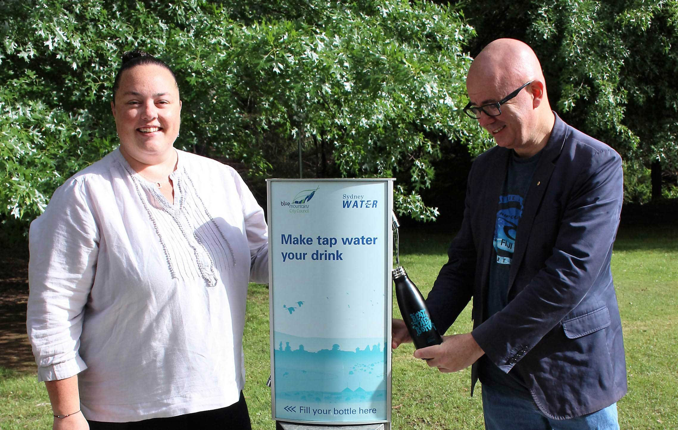 Mayor, Cr Mark Greenhill and Sydney Water rep, Amy Bromhead, try one of the water refill stations in Maple Grove Park, Katoomba. The partnership is making tap water more accessible in popular public places.