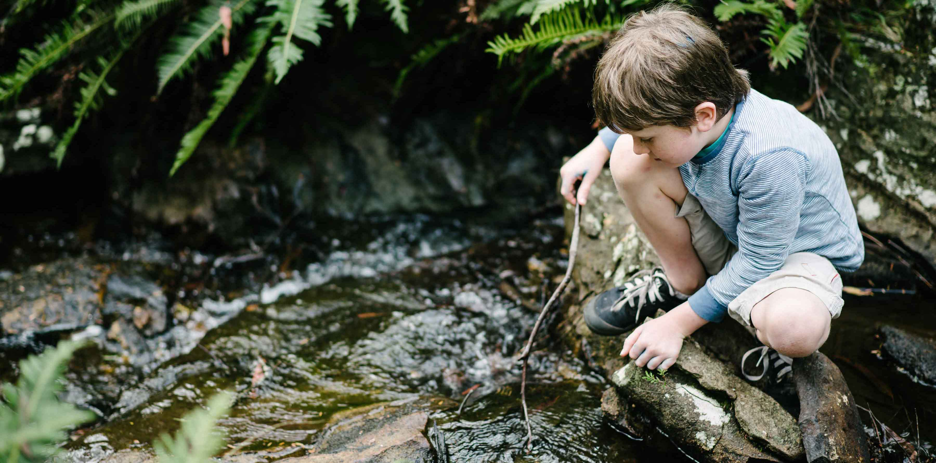Young boy playing in a stream