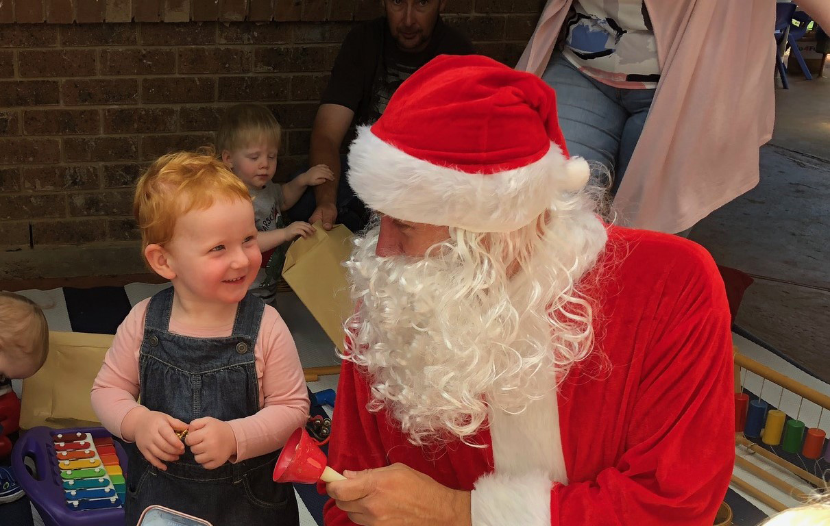 Santa pays an early visit to the children at the Blaxland Family Day Care office for its annual end-of-year celebration.