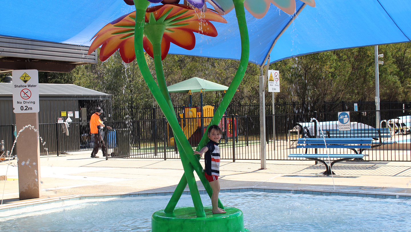 A toddler enjoying the new spray feature at Lawson Swim Centre.
